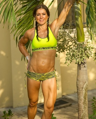 Fitness trainer Jodi Rund in th tropics posing next to a palm tree