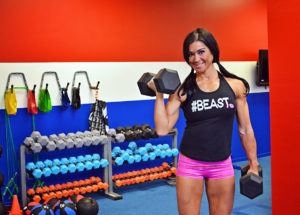 Picture of Fitness model, Jodi Rund, Pink shorts, Black tank top, lifting weights
